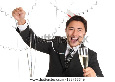 Young man wearing a suit, tie and party hat, holding a champagne glass. White background. - stock photo