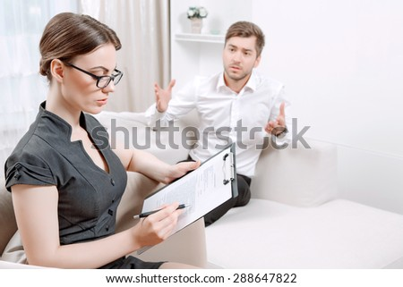 Young man wearing a white shirt sitting on a couch telling his problems and gesticulating, psychologist with clipboard listening to him and making notes during therapy session, selective focus - stock photo