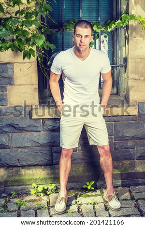 Young man. Wearing a white V neck T shirt, light yellow shorts,  leather shoes, hands in pockets, lowering back, a young guy is standing by a window with green ivy leaves, smiling, looking at you.  - stock photo