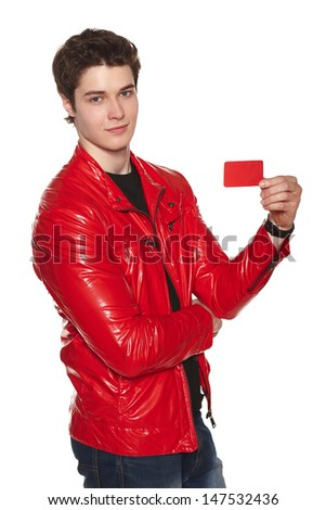 Young man wearing bright red jacket showing blank credit card, over white background - stock photo