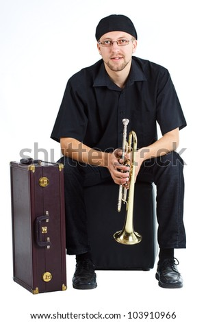 Young man wearing cap and glasses, sitting with a suitcase, holding a trumpet - isolated on white - stock photo