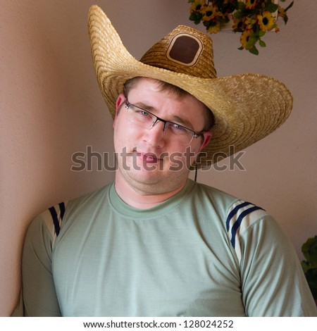 Young man wearing cowboy hat against the wall