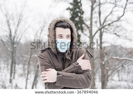 Young man wearing face mask, protection from virus infection in winter time, feeling bad and cold - stock photo