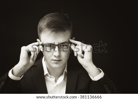 Young man wearing glasses and a business suit. - stock photo
