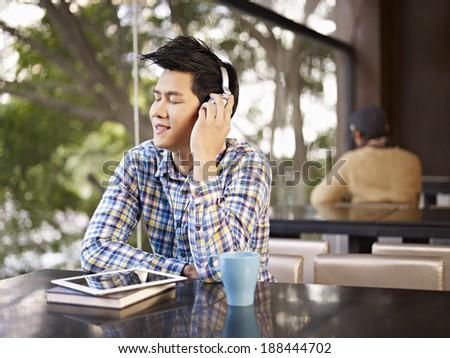 young man wearing headphone enjoying music in cafe - stock photo
