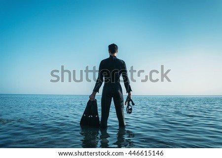 Young man wearing in a diving suit with a mask and flippers standing in the sea and looking into the distance in summer, rear view - stock photo