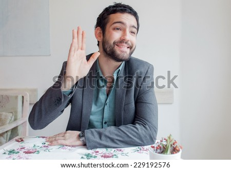 Young man wearing jacket sitting in restaurant and calling waiter. - stock photo