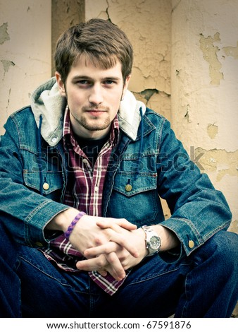 Young man wearing jeans clothes sits in front of the cracked wall. - stock photo