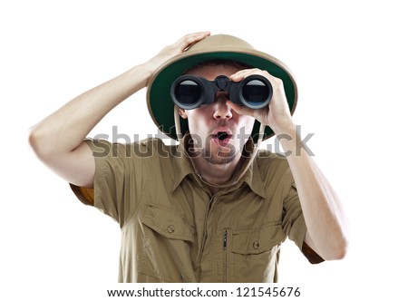 Young man wearing safari shirt and pith helmet looking through binoculars with a surprised expression, isolated on white - stock photo