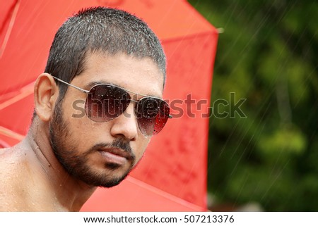 Young man wearing sun glass  back grounded by umbrella
