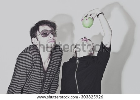 Young man wearing sunglasses and woman biting a green apple