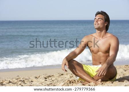 Young Man Wearing Swimming Costume Sitting On Beach - stock photo