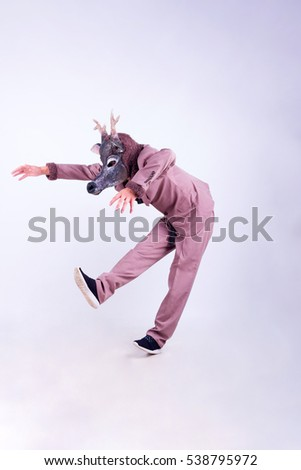 Young man wearing the mask of deer dancing isolated on white background