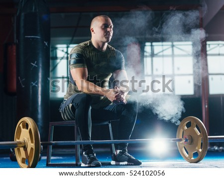 Young man weightlifter preparing for training with barbells at gym. CrossFit.