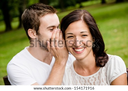 Young man whispering to woman (girlfriend) - outdoor lifestyle photo - stock photo