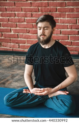 Young man with a beard and closed eyes wearing black T-shirt and blue trousers doing yoga position on blue matt at wall background, copy space, portrait, meditating - stock photo