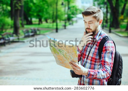Young man with a beard holding a map and thinking, outdoors in the alley of the park - stock photo
