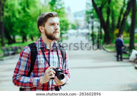 Young man with a beard holding old film camera and looking to the side, outdoors in the alley, in the park, profile - stock photo