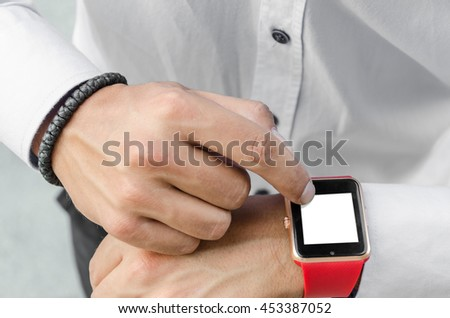 young man with a beard in a shirt utilizes a smart watch