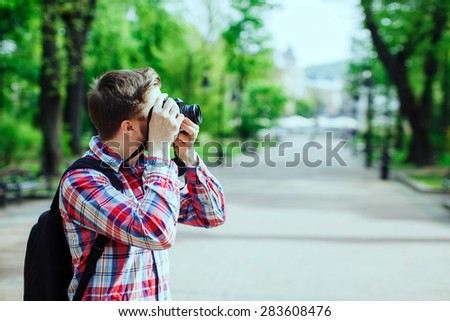 Young man with a beard taking photos on old film camera outdoors in the alley, in the park, profile - stock photo