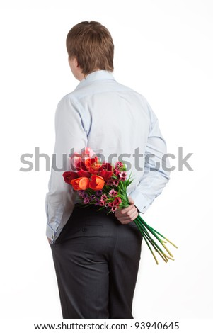 young man with a bouquet of tulips behind - stock photo