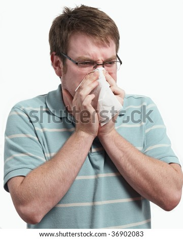 Young man with a cold blowing nose on tissue - stock photo