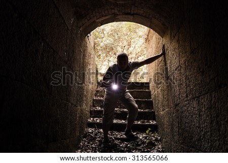 Young man with a flashlight enters the stone tunnel and looks in the dark, warm tonal correction photo filter effect - stock photo