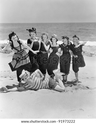 Young man with a group of young women at the beach - stock photo