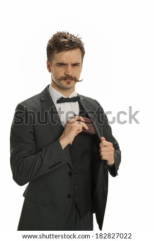 Young man with a handlebar mustache and pin-striped suit pulls out his wallet - stock photo