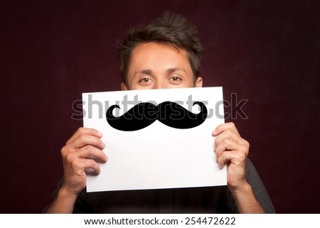 Young man with a happy smiley card half covering face with large false mustache like a hipster - stock photo
