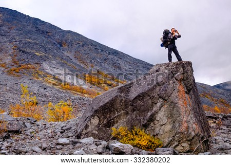 Young man with a heavy backpack makes a landscape picture with a compact retro digital camera on top of a huge rock in Hibiny mountains above the Arctic circle, Kola peninsula, Russia