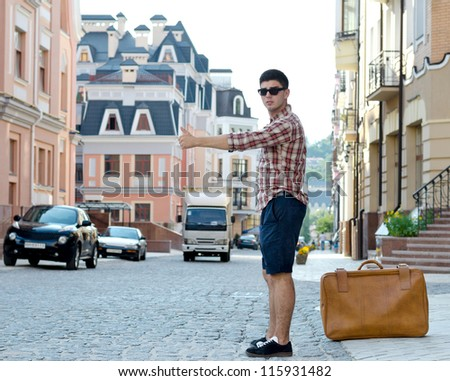 Young man with a large suitcase thumbing a ride in an urban street with historic buildings as he hitchhikes his way around the country - stock photo