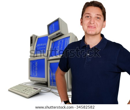 Young man with a pile of computers in the background - stock photo