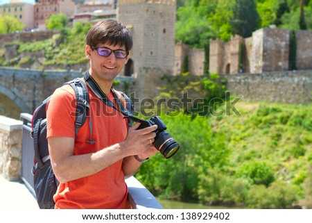 Young man with a professional digital camera, an ancient city wall in the background, Toledo, Spain - stock photo