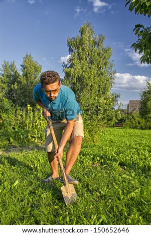 young man with a shovel digging a vegetable garden