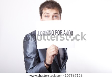 Young man with a sign looking for a job. - stock photo