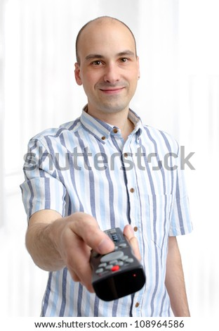 young man with a TV remote - stock photo