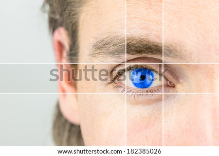 Young man with a vivid blue eye with parallel lines drawing your attention in a conceptual image of mental perception, visionary, intelligence or optics and eyesight. - stock photo