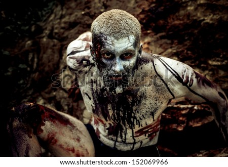 young man with a zombie body painting, covered with blood on the beach against a cliff - stock photo