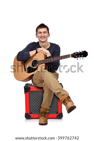young man with acoustic guitar sitting on combo amp