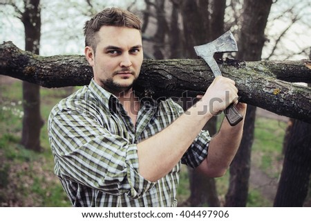 Young man with an ax and log on a shoulder - stock photo