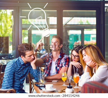 Young man with an idea, sitting with his friends in a cafe - stock photo