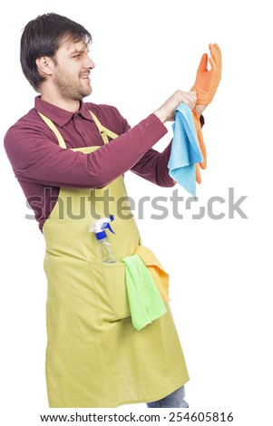Young man with apron putting his household gloves, ready to clean , against white - stock photo