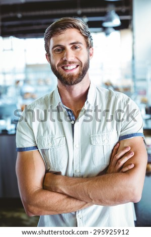 Young man with arms crossed looking the camera at the cafe - stock photo