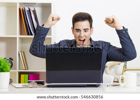 young man with arms raised with computer laptop enthusiastically celebrating success