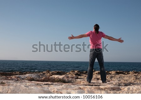 young man with arms wide open affirmating the sea - stock photo
