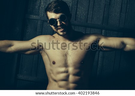 Young man with athletic muscular body and bare sexy torso in swimming glasses.