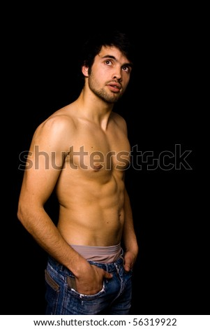 Young man with atletic body on black background - stock photo