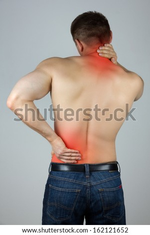Young man with back and neck pain in the red zone - stock photo