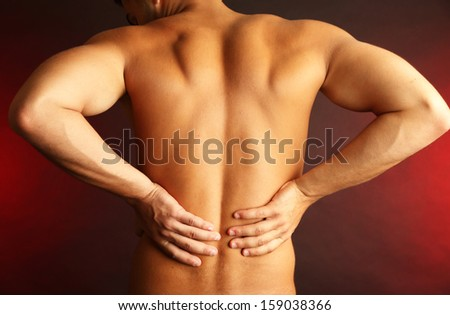 Young man with back pain on dark background - stock photo
